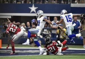 Atlanta Falcons cornerback Robert Alford (23) and cornerback Desmond Trufant (21) are sent flying along with Dallas Cowboys wide receiver Devin Street (15) as running back Joseph Randle (21) scores a touchdown on a running play during the first half of an NFL football game on Sunday, Sept. 27, 2015, in Arlington, Texas. (AP Photo/Michael Ainsworth )