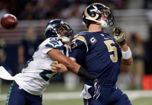 St. Louis Rams quarterback Nick Foles, right, fumbles as he is hit by Seattle Seahawks defensive back Cary Williams while throwing during the fourth quarter of an NFL football game Sunday, Sept. 13, 2015, in St. Louis. Williams recovered the fumble and returned the ball for a touchdown. (AP Photo/Tom Gannam)