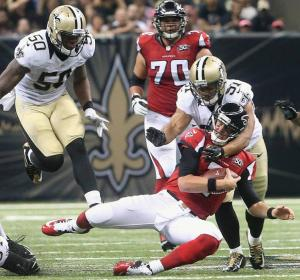 New Orleans Saints outside linebacker Kasim Edebali (91) hits Atlanta Falcons quarterback Matt Ryan (2) during the first half of an NFL football game, Thursday, Oct. 15, 2015, in New Orleans. (AP Photo/John Bazemore)