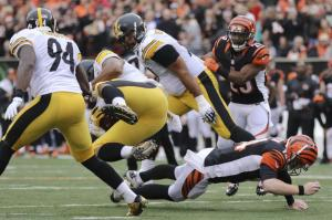Cincinnati Bengals quarterback Andy Dalton, right, tackles Pittsburgh Steelers defensive end Stephon Tuitt, center left, after Tuitt caught an interception in the first half of an NFL football game, Sunday, Dec. 13, 2015, in Cincinnati. (AP Photo/Gary Landers)