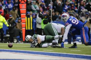 New York Jets quarterback Ryan Fitzpatrick (14) watches the ball he fumbled on a Buffalo Bills' Mario Williams (94) sack during the first half of an NFL football game Sunday, Jan. 3, 2016, in Orchard Park, N.Y. (AP Photo/Bill Wippert)